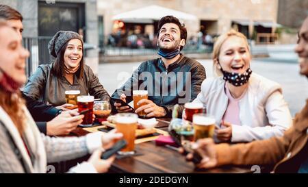 Giovani amici bere birra indossando maschera viso - nuovo normale concetto di stile di vita con le persone che si divertono insieme a parlare su felice ora in birreria all'aperto
