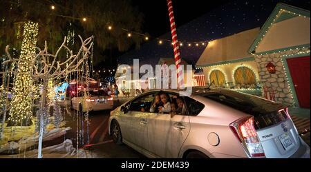 I bambini guardano fuori dalla finestra posteriore di un'automobile a Wonderland, un'esperienza drive-thru a tema di festa, durante lo scoppio della malattia del coronavirus (COVID-19), in Woodland Hills, California, Stati Uniti, 30 novembre 2020. Foto scattata il 30 novembre 2020. REUTERS/Mario Anzuoni