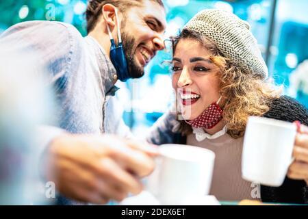 Felice coppia con maschera viso divertirsi insieme al bar Caffetteria - nuovo concetto di stile di vita normale con i giovani che parlano e bere caffè americano