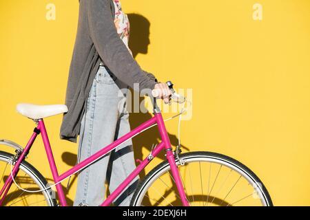 giovane donna irriconoscibile che cammina con una bici rosa retrò di fronte a una parete colorata gialla, concetto di stile di vita attivo e mobilità sostenibile, co