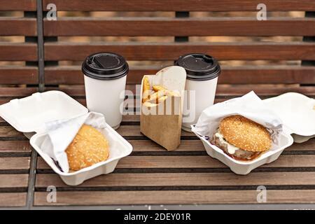 Fast food. Tazze di carta con caffè, scatole di hamburger e patatine fritte su un concetto di cibo pank.Takeaway Park.