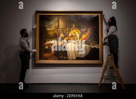 Gli assistenti della galleria regolano 'UNA vita still del banchetto' da Jan Davidsz De Heem con una stima di ??4-6 milioni, che è in mostra alla saleroom di Christie nel centro di Londra prima delle vendite della casa d'aste della settimana classica imminente.