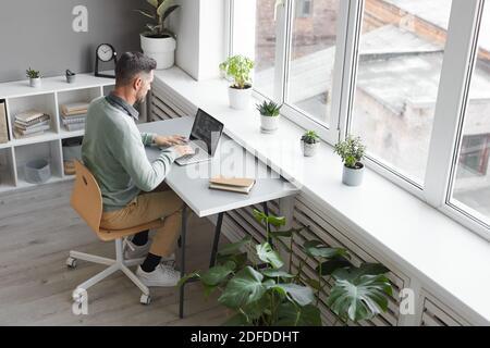 Programmatore di computer seduto sul suo posto di lavoro che scrive sul laptop dentro ufficio spazioso Foto Stock