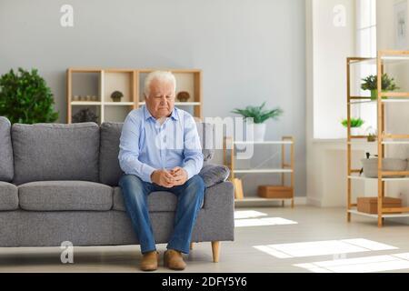 Uomo anziano seduto sul divano a casa sentendosi depresso, solitario e abbandonato dalla sua famiglia