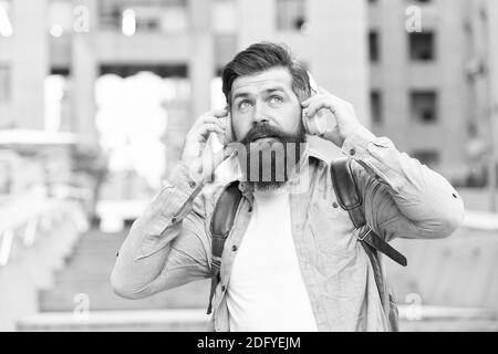 Abbiamo le orecchie per le strade. L'uomo con la bearded indossa auricolari all'aperto. Hipster consente di ascoltare la musica con le cuffie. Cuscinetti comodi. Protezione dell'udito. Vita moderna. Conoscenza dell'orecchio per la vostra anima. Foto Stock