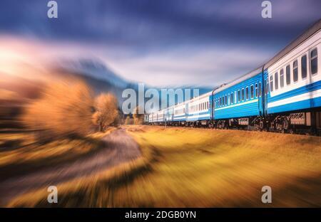 Treno in movimento in montagna al tramonto con effetto di sfocatura del movimento Foto Stock