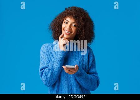 HMM interessante. Intrigato e sognante, creativo afro-american ragazza think-up natale messaggio di congratulazioni, tenendo smartph