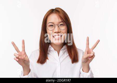 Primo piano ritratto di allegra donna asiatica in occhiali, sorridente kawaii mostrando gesto di pace, segno di buona volontà, espressa positività ha Foto Stock