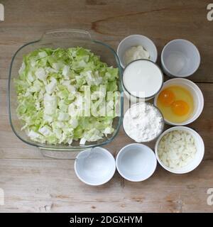 Preparazione della torta di cavolo ricetta passo-passo alimenti ingredienti su tavola di legno sfondo vista dall'alto piatto posato. Primo piano. Messa a fuoco selettiva. Spazio di copia Foto Stock