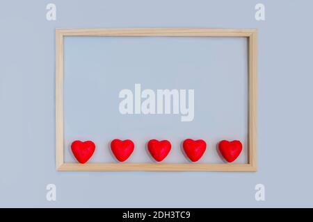 Concetto di giorno e amore di San Valentino: Cornice rettangolare in legno con cuori rossi all'interno su sfondo azzurro. Vista dall'alto, primo piano, macro. Foto Stock