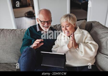 Sorridi una coppia anziana che utilizza un tablet digitale mentre si siede sul divano in soggiorno