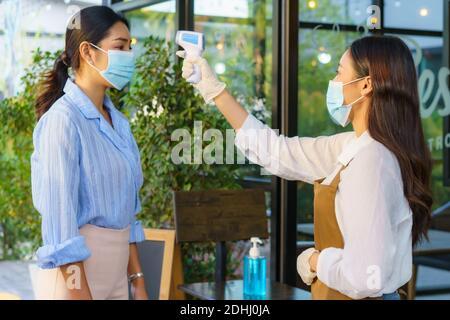Donna asiatica impiegato caffè prendere temperatura asiatica donna con faccia maschera prima di andare al ristorante o caffè per nuovo stile di vita normale coronavirus cov