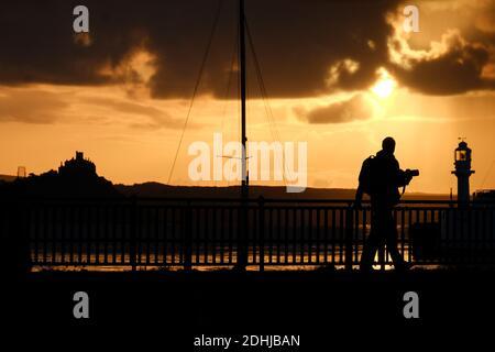 Un fotografo cattura la calma prima di Storm Alex, mentre il sole sorge dietro il faro del porto di Penzance il primo giorno di ottobre.