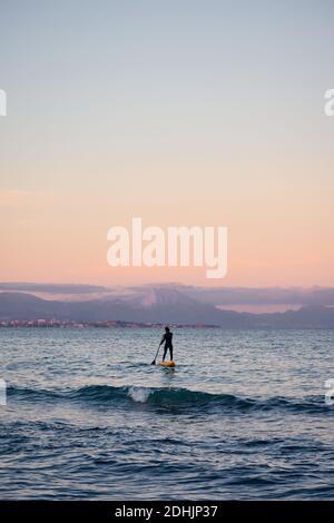 Surfista maschile in muta canottiera su tavola a pale in mare acqua sullo sfondo delle montagne al tramonto Foto Stock