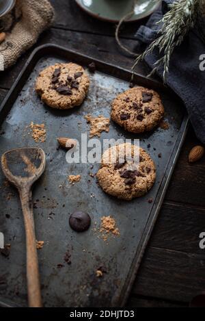 Dall'alto di squisiti biscotti fatti in casa con patatine al cioccolato e mandorle su lamiera da forno su tavola di legno Foto Stock