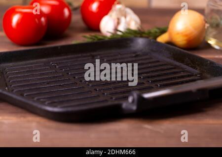 teglia vuota, accanto a pomodori, cipolle e aglio su un tavolo di legno. Foto Stock