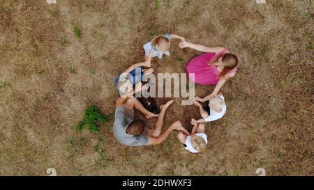 Una famiglia cordiale che agitava le mani mentre si siede sull'erba con un cane. Vista dal drone.