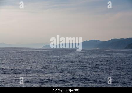 Una vista dal mare verso le montagne con nebbia di mare Foto Stock