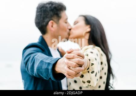 Coppia baciando le mani di tenuta con anello di fidanzamento di nozze che mostra con facce in primo piano di sfondo