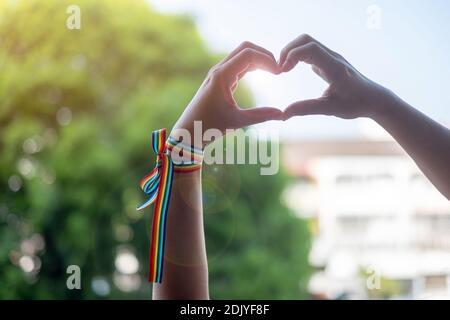 Vista ad angolo basso delle mani che creano una forma cardiaca all'aperto