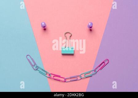 Direttamente sopra la foto del viso Smiley realizzata con materiali di consumo per ufficio su sfondo multicolore