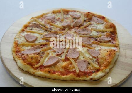 pizza con salsicce, cetrioli, pepe, formaggio, cipolla isolata su fondo bianco di legno. Pubblicità per la rete sociale di ristoranti, caffè. Promozione Foto Stock