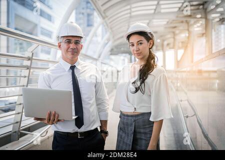 senior manager e donna operatrice con casco di sicurezza incontro vedere il brainstorming del laptop lavora fuori dalla fabbrica Foto Stock
