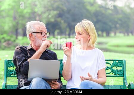 Felice coppia senior nel parco tenendo il cuore in amore San Valentino concetto di giorno Foto Stock