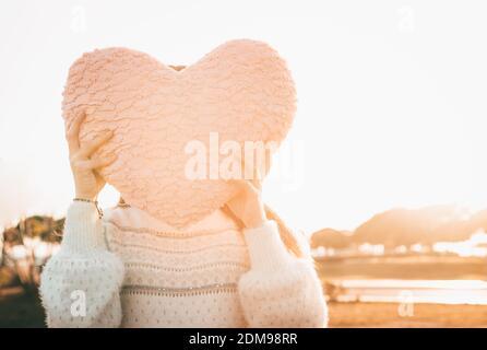 Ragazza che tiene UN cuscino a forma di cuore rosa che copre la sua faccia