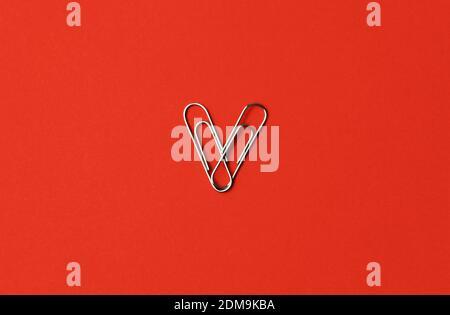 La carta a forma di cuore si aggancia su uno sfondo rosso. Concetto di San Valentino. Foto di alta qualità