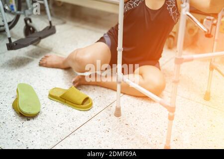 Asian di mezza età lady donna caduta del paziente nel soggiorno perché le superfici scivolose