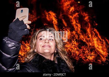 Donna che prende Selfie contro Bonfire di notte