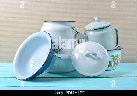 Un sacco di piatti smaltati su un tavolo blu. Utensili da cucina in stile retrò