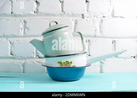 Lot of enameled dishes on a blue table against white brick wall background. Retro style cookware