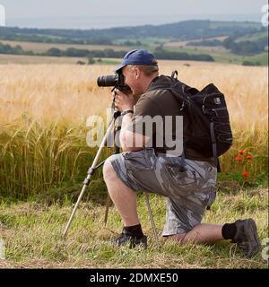 Fotografo maschio inginocchiato da un campo di orzo guardando attraverso la sua fotocamera montata su un treppiede. Paesaggio formato quadrato con colline sullo sfondo.