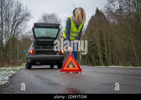 Giovane donna bionda in una giacca invernale in un giubbotto giallo mette un segnale di arresto di emergenza sulla strada un triangolo arancione vicino a un'auto con bagagliaio aperto Foto Stock
