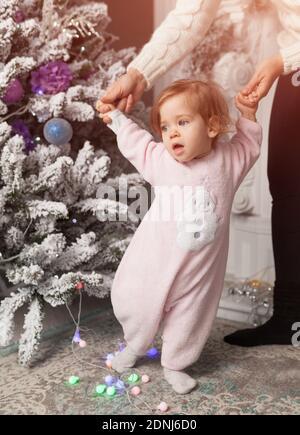 Sezione bassa della ragazza che assiste della madre per camminare a casa durante Natale