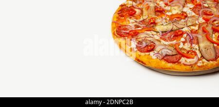 Gustosa pizza al pepe piccante servita su un piatto di legno, ingredienti salsa Signature, mozzarella, pepperoni, cetriolo sottaceto, pepe bulgaro, cipolla rossa, peperoncino. Poster promozionale pizzeria. Foto Stock