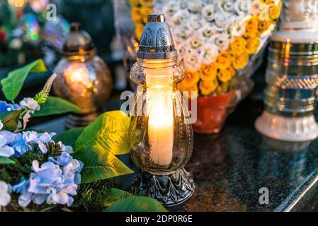 Fiori artificiali e candelabri giacciono sulla Tombstone nel Cimitero.