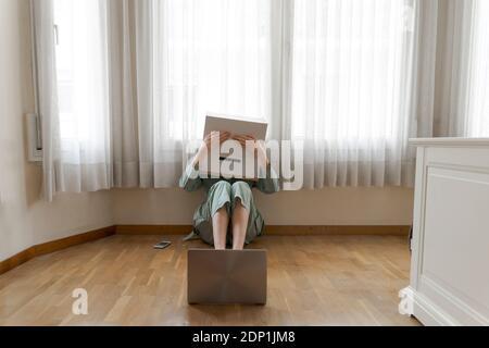 Donna che indossa una scatola di carte sulla testa con sorriso annoiato seduto sul pavimento di fronte al computer portatile, che copre gli occhi Foto Stock