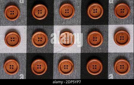 Bottoni da cucire rotondi di legno marrone isolati su fondo tessile. Vista dall'alto . Primo piano. Macro.