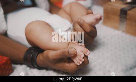 Cute baby feet nelle mani di nero padre circondato da regali di natale, primo piano. Foto di alta qualità