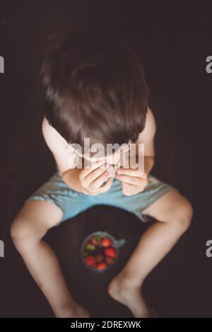 Vista ad alta angolazione di Shirless Boy mangiare frutta contro sfondo nero