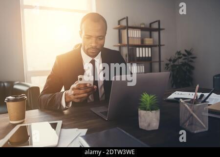 Ritratto dell'uso del avvocato del mediatore dell'uomo americano afro del pensivo messo a fuoco smartphone chattare con i clienti partner indossare tuta tux tuxedo in luogo di lavoro