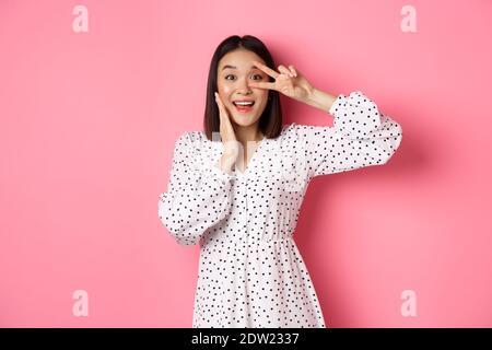 Bella e femminile donna asiatica mostrando kawaii segno sull'occhio e guardando stupito alla macchina fotografica, in piedi in abito su sfondo rosa Foto Stock