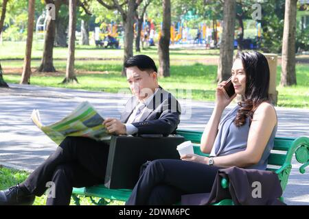 Uomini d'affari seduti sul panca di Park
