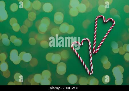 Caramelle natalizie su sfondo verde, lollipop rosso bianco Foto Stock