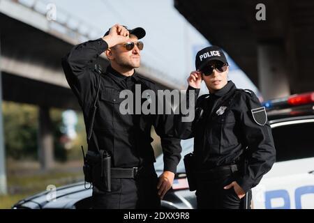 Ufficiali di polizia in occhiali da sole in piedi vicino alla macchina su sfondo sfocato all'aperto