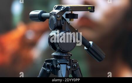 Grande treppiede nero professionale con testa girevole su un occupato via Foto Stock