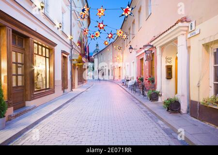 Vista notturna di via Stikliai illuminata nel quartiere ebraico della città vecchia di Vilnius, Lituania.